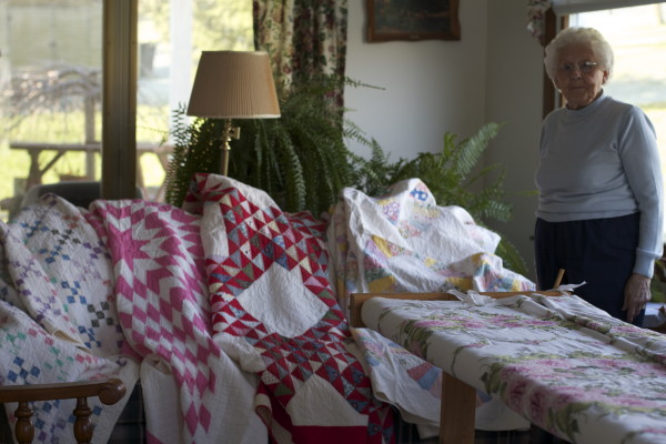 Interviewee Juanita Shockey Harris stands before her family's heirloom quilts.